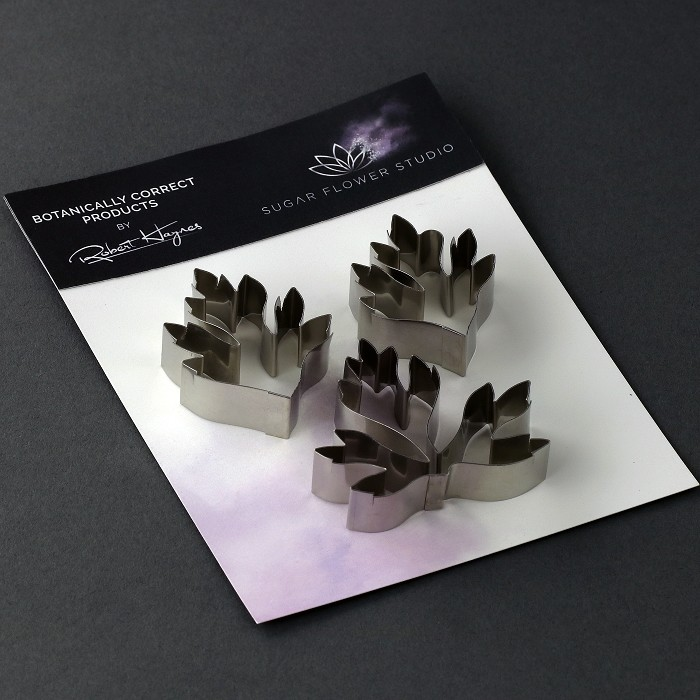 "Buttercup Leaves set of 3 stainless-steel cutter measurements – small leaf length 4.6 cm x width 3.1 cm, medium leaf length 4.1 cm x width 3.1 cm, large leaf length 4.5 cm x width 2.6 cm. (small leaf length 1 13/16"" x width 1 1/4"", medium leaf length 1 5/8"" x width 1 1/4"", large leaf length 1 3/4"" x width 1""). This distinctive range of Botanically Correct Products By Sugar Flower Studio are designed by master sugar artist Robert Haynes. These quality products can be used to replicate time and again, stunning life like flora in any edible or non-edible medium of your choice. The stainless-steel cutters in the Sugar Flower Studio range are perfectly matched to fit within the perimeters of each corresponding silicone veiner, giving you a time efficient and botanically correct result each time. These cutters can be used with edible mediums including sugar flower paste (SFP) gum paste, fondant, modelling chocolate and marzipan. They can also be used with non-edible modelling mediums: cold porcelain (Modena), Hearty - Artista soft, polymer clay and modelling clay. Instructions for use of products: Using the Sugar Flower Studio Hand saver, place on top of each cutter, cut out petals or leaves. Place thinned out petal or leaf shape into lightly corn-floured Sugar Flower Studio veiner. Press firmly to give a natural vein. Remove petal or leaf and allow medium to go leathery before colouring. To clean cutters, wipe with an alcohol dampened soft cloth after each use. Copyright © 2016 Sugar Flower Studio."
