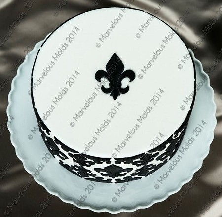 "Fleur de Lis Medallion Onlay, by Chef Dominic Palazzolo of Marvelous Molds, measures 2"" x 2 1/2"". This FDA approved silicone Onlay will transfer its precise raised design onto most surfaces, perfectly every time. Onlays are great for sugar art related mediums, such as fondant, modeling chocolate and gumpaste."