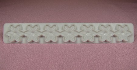 "Flower Embosser is made of plastic and measures 5 1/2"" x 3/4""."