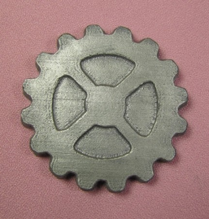 "Gear Steampunk Large, by CakeStructure, measures 2 1/2"" x 2 1/2"" x 1/4""."