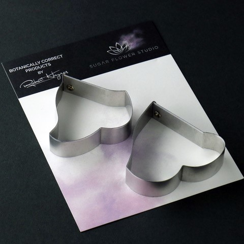 "Glacier Variegated Ivy Leaf aluminum metal cutter Medium set of 2 measurements - medium leaf length 4.8 cm x width 5.2 cm, large leaf length 5.1 cm x width 6.1 cm. (medium leaf length 1 7/8"" x width 2 1/16"", large leaf length 2"" x width 2 3/8""). This distinctive range of Botanically Correct Products By Sugar Flower Studio are designed by master sugar artist Robert Haynes. These quality products can be used to replicate time and again, stunning life like flora in any edible or non-edible medium of your choice. The Aluminium metal cutters in the Sugar Flower Studio range are perfectly matched to fit within the perimeters of each corresponding silicone veiner, giving you a time efficient and botanically correct result each time. These cutters can be used with edible mediums including sugar flower paste (SFP) gum paste, fondant, modelling chocolate and marzipan. They can also be used with non-edible modelling mediums: cold porcelain (Modena), Hearty - Artista soft, polymer clay and modelling clay. Instructions for use of products: Using the Sugar Flower Studio Hand saver, place on top of each cutter, cut out petals or leaves. Place thinned out petal or leaf shape into lightly corn-floured Sugar Flower Studio veiner. Press firmly to give a natural vein. Remove petal or leaf and allow medium to go leathery before colouring. To clean cutters, wipe with an alcohol dampened soft cloth after each use. Copyright © 2016 Sugar Flower Studio."