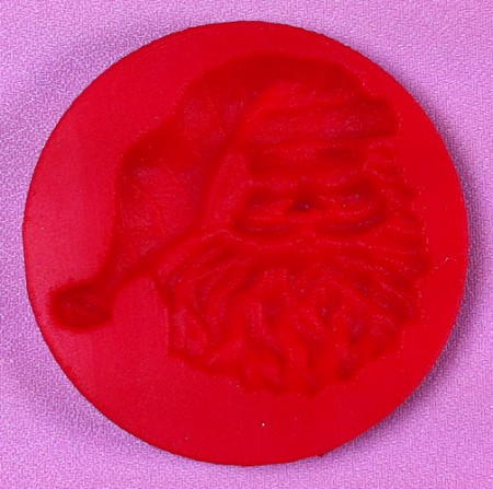 "Santa Face, by Cake Structure, measures 2 1/2"" x 2""."