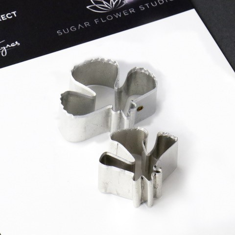 "Scabious petal aluminium metal cutter set of 2 measurements - small petal length 2.4 cm x width 3 cm, large petal length 3.5 cm x width 2.5 cm. (small petal length 1"" x width 1 1/4"", large petal 1 3/8"" width 1"").  This distinctive range of Botanically Correct Products By Sugar Flower Studio are designed by master sugar artist Robert Haynes. These quality products can be used to replicate time and again, stunning life like flora in any edible or non-edible medium of your choice. The aluminium metal cutters in the Sugar Flower Studio range are perfectly matched to fit within the perimeters of each corresponding silicone veiner, giving you a time efficient and botanically correct result each time. These cutters can be used with edible mediums including sugar flower paste (SFP) gum paste, fondant, modelling chocolate and marzipan. They can also be used with non-edible modelling mediums: cold porcelain (Modena), Hearty - Artista soft, polymer clay and modelling clay. Instructions for use of products: Using the Sugar Flower Studio Hand saver, place on top of each cutter, cut out petals or leaves. Place thinned out petal or leaf shape into lightly corn-floured Sugar Flower Studio veiner. Press firmly to give a natural vein. Remove petal or leaf and allow medium to go leathery before colouring. To clean cutters, wipe with an alcohol dampened soft cloth after each use. Copyright © 2016 Sugar Flower Studio."