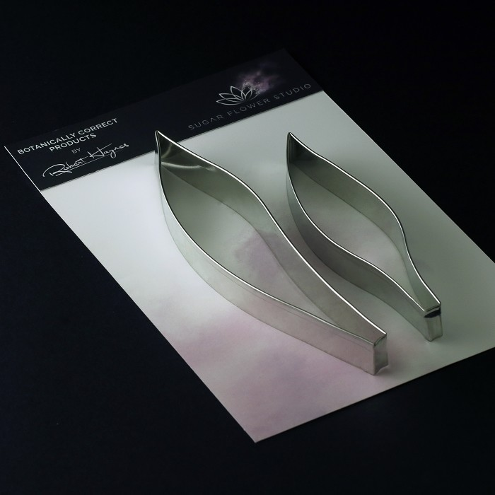 "Tulip Leaf rolled edge metal small cutter set of 2 measurements –smaller leaf length 12.2 cm x width 2.7 cm, larger leaf length 16 cm x width 3.5 cm. (smaller leaf length 4 3/4"" x width 1 1/8"", larger leaf length 6 3/8"" x width 1 3/8"") This distinctive range of Botanically Correct Products By Sugar Flower Studio are designed by master sugar artist Robert Haynes. These quality products can be used to replicate time and again, stunning life like flora in any edible or non-edible medium of your choice. The rolled edge cutters in the Sugar Flower Studio range are perfectly matched to fit within the perimeters of each corresponding silicone veiner, giving you a time efficient and botanically correct result each time. These cutters can be used with edible mediums including sugar flower paste (SFP) gum paste, fondant, modelling chocolate and marzipan. They can also be used with non-edible modelling mediums: cold porcelain (Modena), Hearty - Artista soft, polymer clay and modelling clay. Instructions for use of products: Using the Sugar Flower Studio Hand saver, place on top of each cutter, cut out petals or leaves. Place thinned out petal or leaf shape into lightly corn-floured Sugar Flower Studio veiner. Press firmly to give a natural vein. Remove petal or leaf and allow medium to go leathery before colouring. To clean cutters, wipe with an alcohol dampened soft cloth after each use. Copyright © 2016 Sugar Flower Studio."