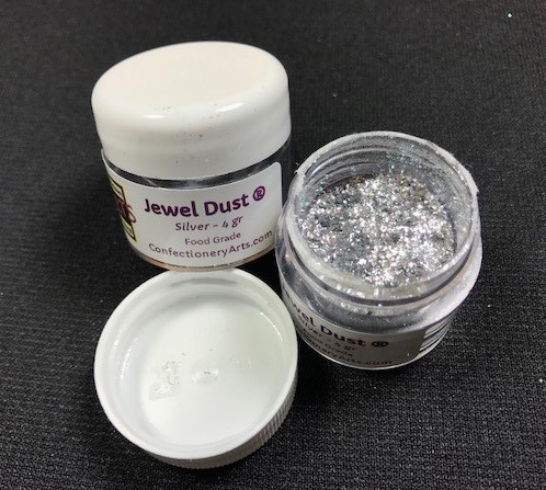 Silver Jewel Dust, by CAI, contains 4 grams of Jewel Dust. This Jewel Dust is on fire and is absolutely brilliant, like a diamond! Jewel Dust is made of all FDA approved ingredients and 100% edible.  It will provide bling and sparkle to any project.
